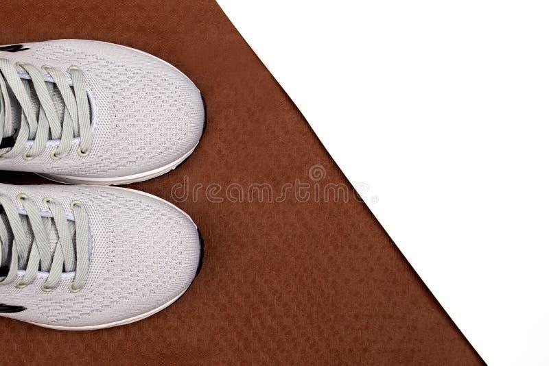 Witte tennisschoenen op een bruine achtergrond De tennisschoenen van mensen op een witte achtergrond Grijze tennisschoenen royalty-vrije stock afbeeldingen