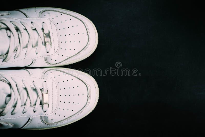 Witte tennisschoenen op zwarte achtergrond royalty-vrije stock afbeelding