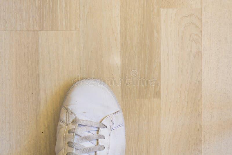 Witte tennisschoenschoen op houten vloer royalty-vrije stock foto's