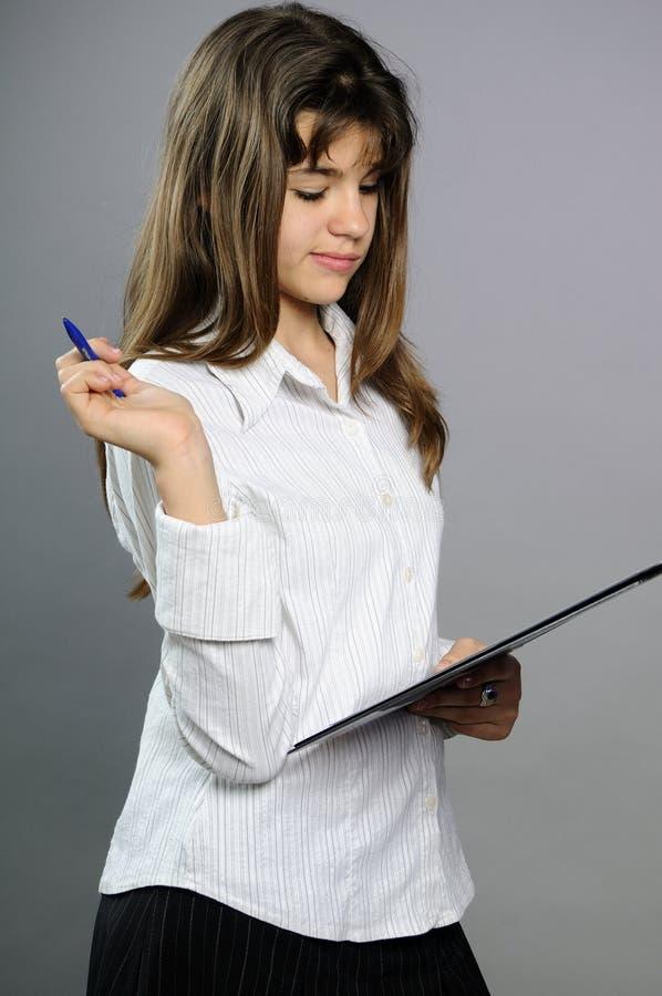 Witte tiener die op papier met pen schrijft stock fotografie