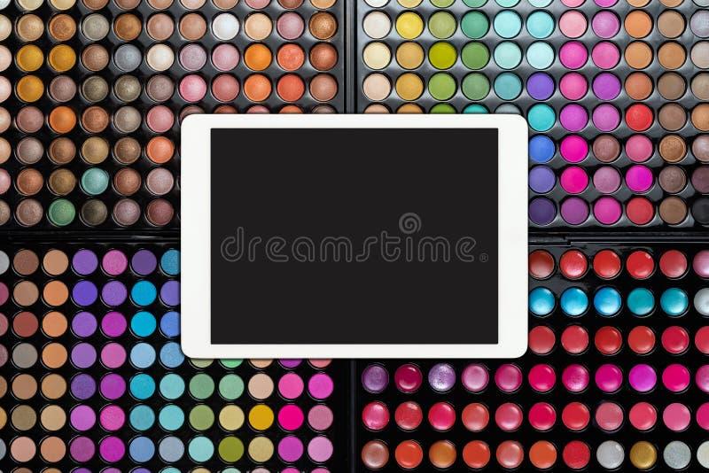 Witte touchpad met het lege scherm op kleurrijke oogschaduwpaletten De paletten van de oogschaduwmake-up met tabletcomputer royalty-vrije stock afbeeldingen