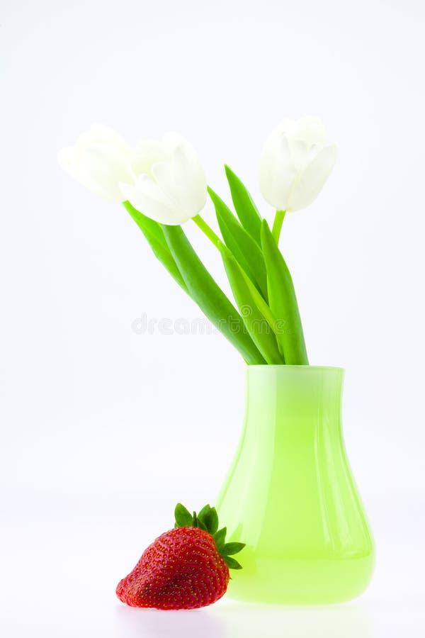 Witte tulpen in een vaas en aardbeien royalty-vrije stock foto's