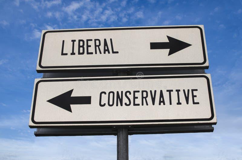 Witte twee straatborden met een pijl op een metalen stok met een woord liberaal en conservatief stock foto's