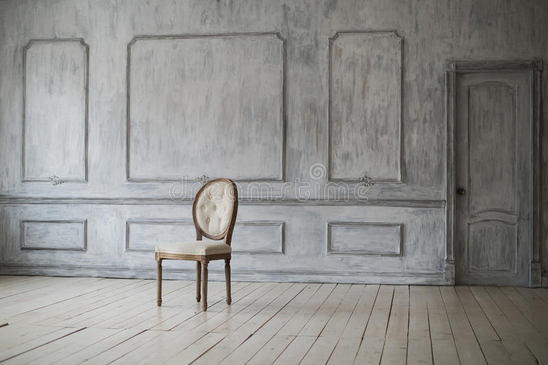 Witte uitstekende stoel die zich voor een lichte muur met afgietsels op houten parketvloer bevinden stock foto's