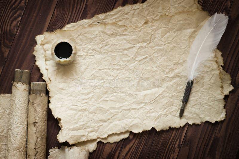 Witte veer en oude rol op bruine plank stock foto's