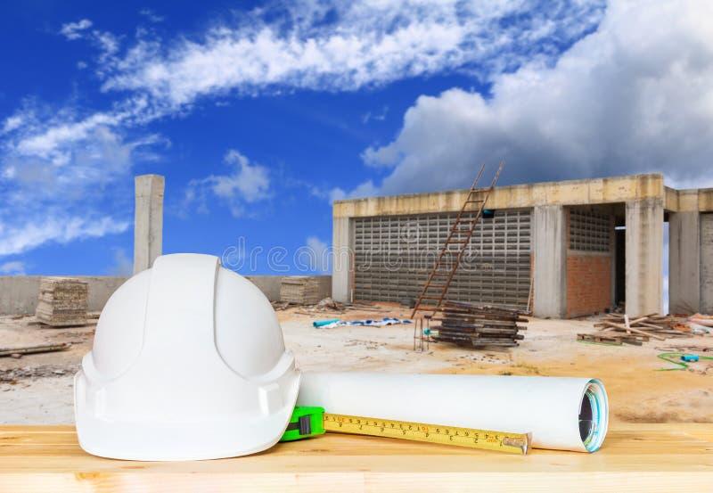 Witte veiligheidshoed en papieren plan blauwdruk op houttafel stock afbeelding