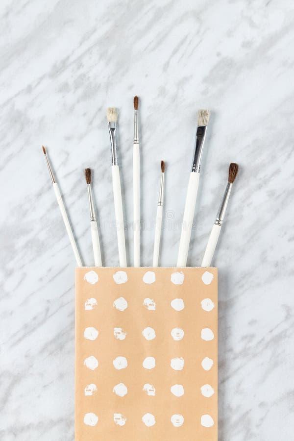 Witte verfborstels in een decoratieve document zak stock foto