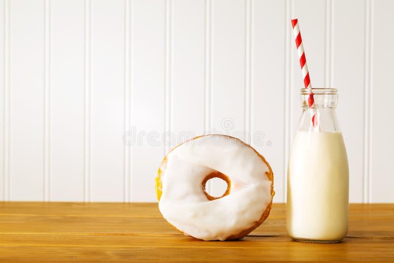 Witte verglaasde doughnut met kruik melk stock foto