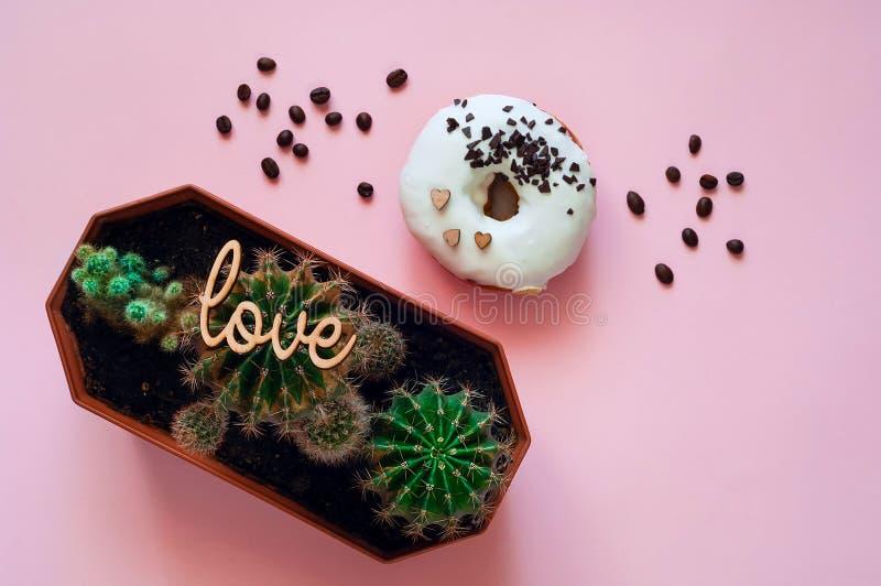 Witte verglaasde doughnut met zwarte chocoladesnoepjes met kleine cactussen Voedsel creatief concept Groene Neonstemming op Roze  stock foto