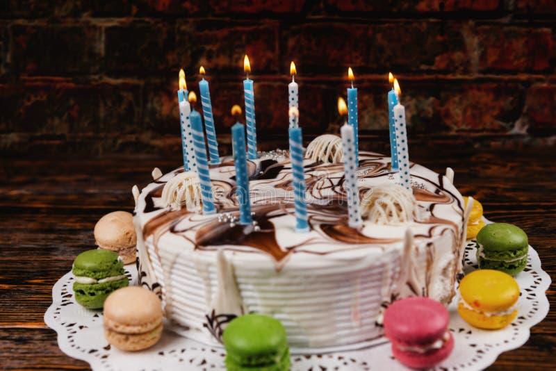 Witte verjaardagscake met veel het branden van kaarsen dichtbij verschillend stock foto