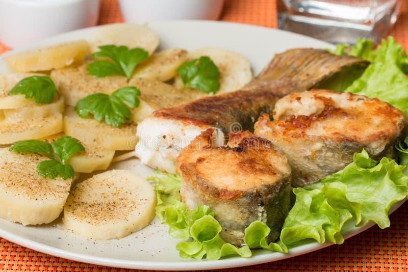 Witte vissen met aardappel op witte plat stock foto