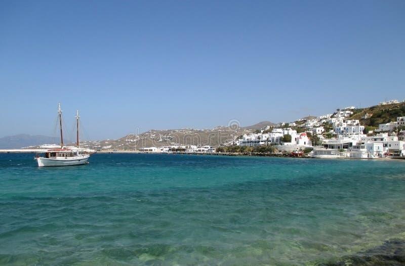 Witte vissersboot en weinig stad tussen de blauwe hemel en het blauwe overzees, Mykonos-Eiland royalty-vrije stock afbeeldingen