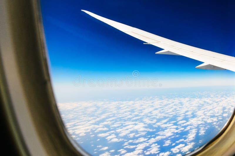Witte vleugel van de vliegtuigenmening van de zetel die van het vliegtuigvenster in de blauwe hemel met witte wolkenachtergrond v stock foto