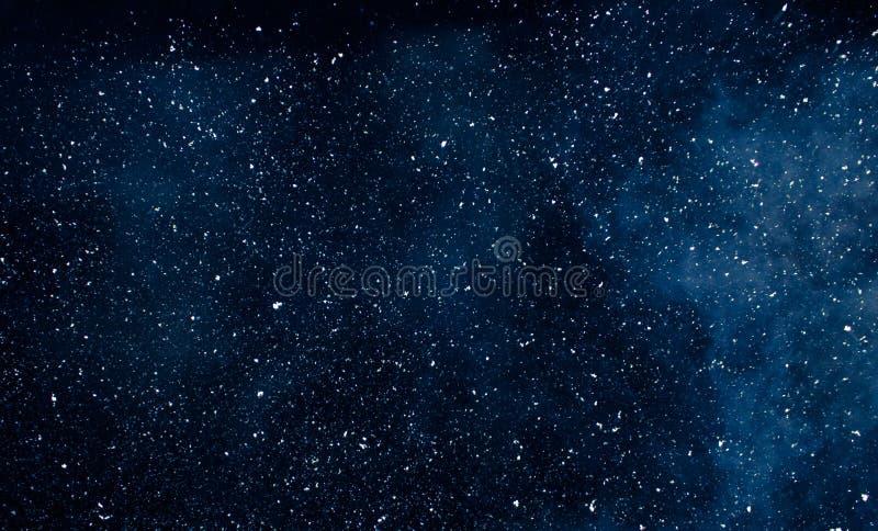 Witte vlokken van sneeuw op een donkerblauwe achtergrond royalty-vrije stock afbeeldingen