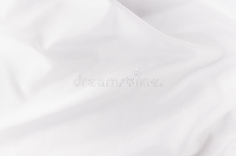 Witte vlotte van het luxezijde of satijn textuur met vloeibare golven voor huwelijksachtergrond stock foto
