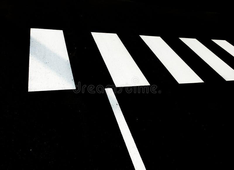Witte voetgangersoversteekplaats op zwarte teer stock afbeeldingen