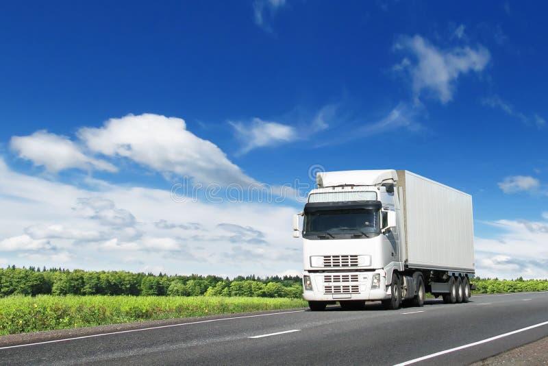 Witte vrachtwagen op landweg onder blauwe hemel stock afbeelding