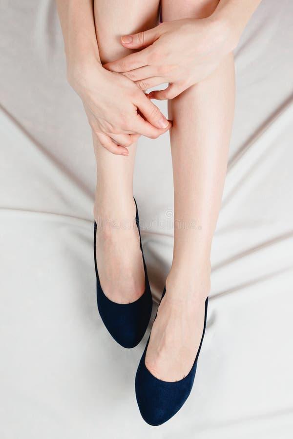 Witte vrouw die haar benen in houden hoog gehielde donkerblauwe schoenen royalty-vrije stock afbeelding