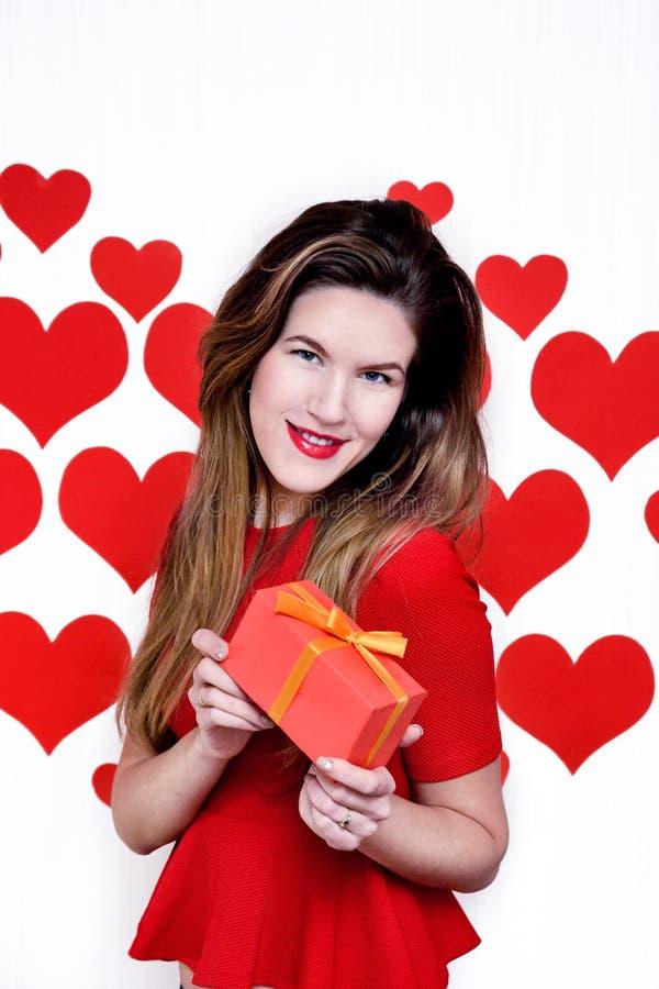 Witte vrouw met rode lippen die een gift op hart gestalte gegeven achtergrond geven De dag van de valentijnskaart `s royalty-vrije stock foto's