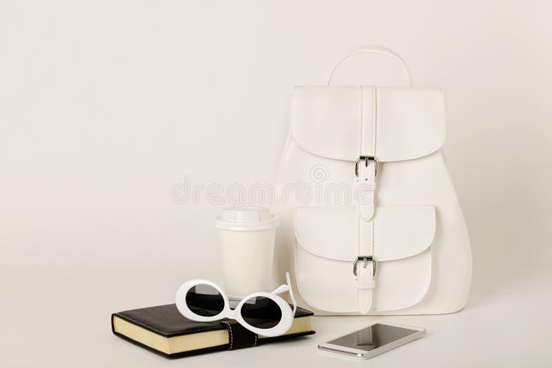Witte vrouwelijke rugzak, smartphone, notitieboekje en zonnebril op a royalty-vrije stock foto