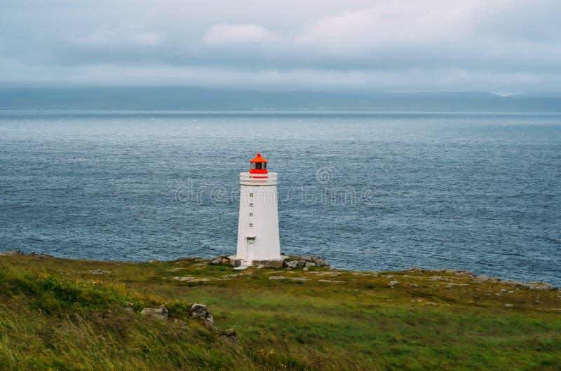 Witte vuurtoren met rood dak in IJsland met oceaanachtergrond royalty-vrije stock foto's