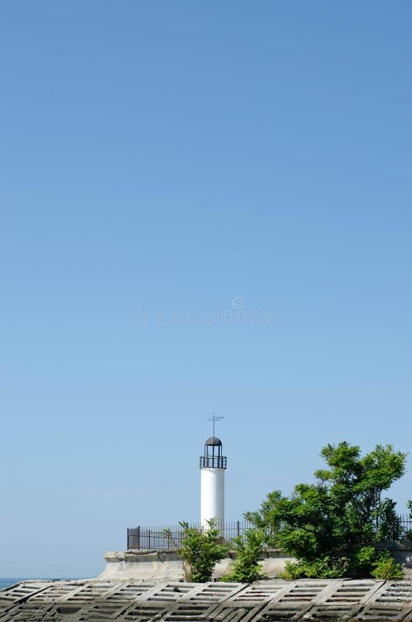 Witte vuurtoren op zee met blauwe lucht royalty-vrije stock foto