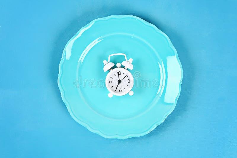 Witte wekker in blauwe lege plaat Tijd om gewicht te verliezen, etend controle of tijd aan dieetconcept stock afbeelding