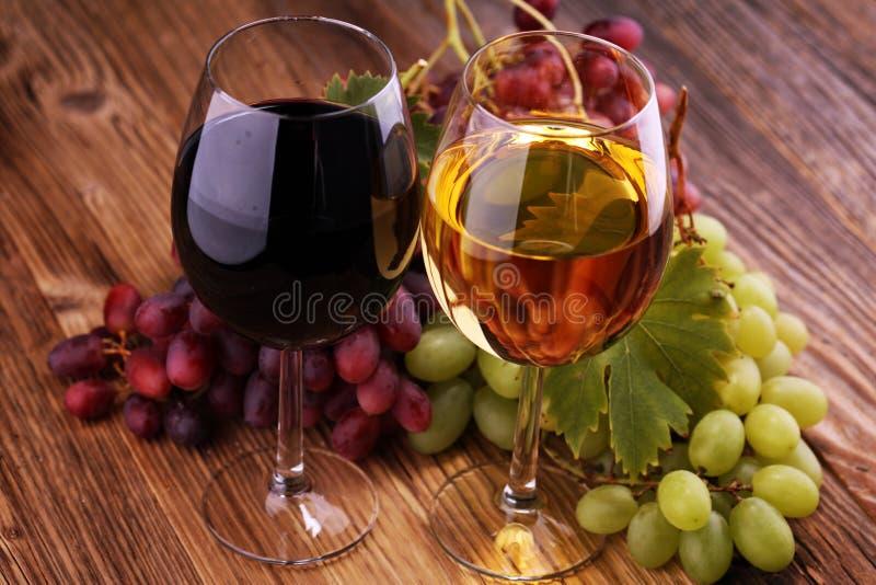 Witte wijn en rode wijn in een glas met dalingsdruiven op rustieke achtergrond royalty-vrije stock afbeelding