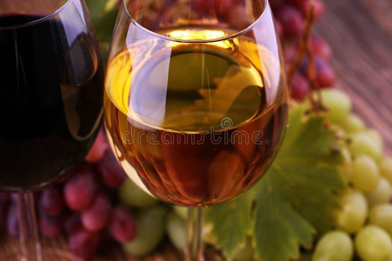 Witte wijn en rode wijn in een glas met dalingsdruiven op rustieke achtergrond royalty-vrije stock foto