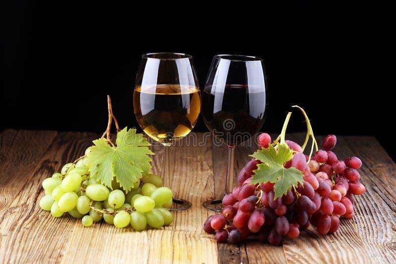 Witte wijn en rode wijn in een glas met dalingsdruiven op rustieke achtergrond stock foto