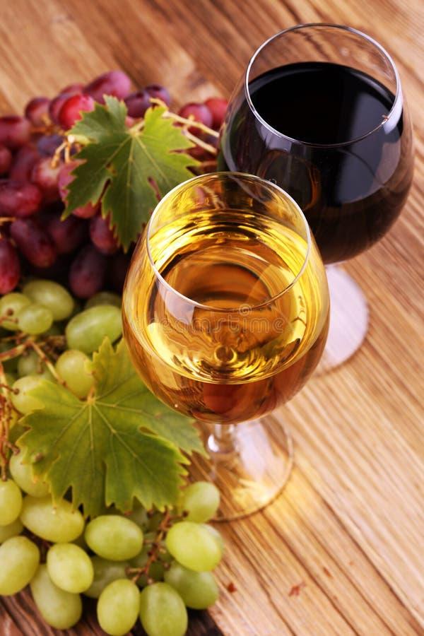 Witte wijn en rode wijn in een glas met dalingsdruiven op rustieke achtergrond stock fotografie