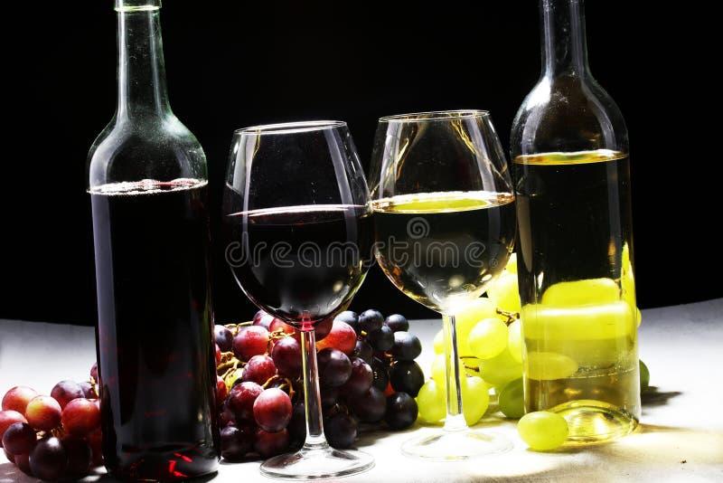 Witte wijn en rode wijn in een glas met dalingsdruiven, witte steen stock foto's
