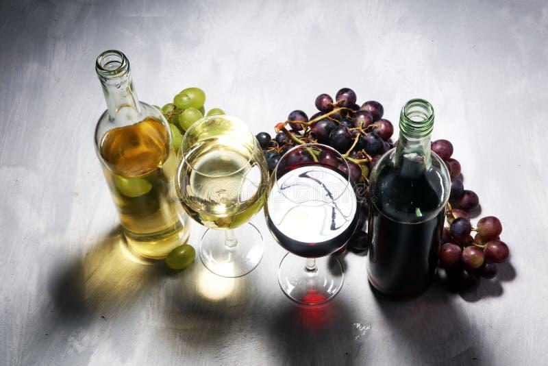 Witte wijn en rode wijn in een glas met dalingsdruiven, witte steen royalty-vrije stock fotografie