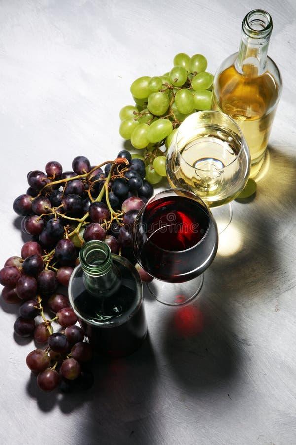 Witte wijn en rode wijn in een glas met dalingsdruiven, witte steen royalty-vrije stock foto's