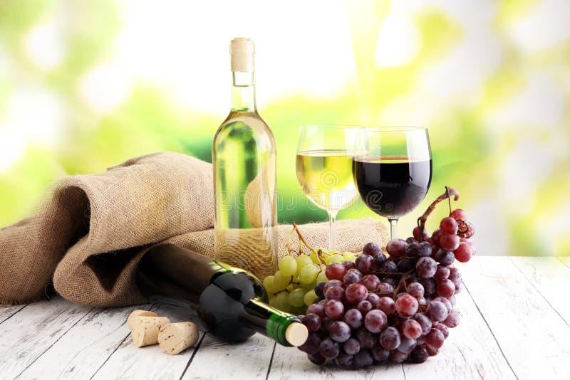 Witte wijn en rode wijn in een glas met dalingsdruiven, witte woode stock foto's