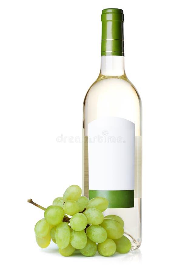 Witte wijn in fles met lege etiket en druiven stock foto's