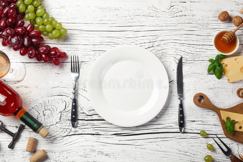 Witte wijnfles, druif, honing, kaas, wijnglas, plaat, mes en vork op witte houten raad stock foto