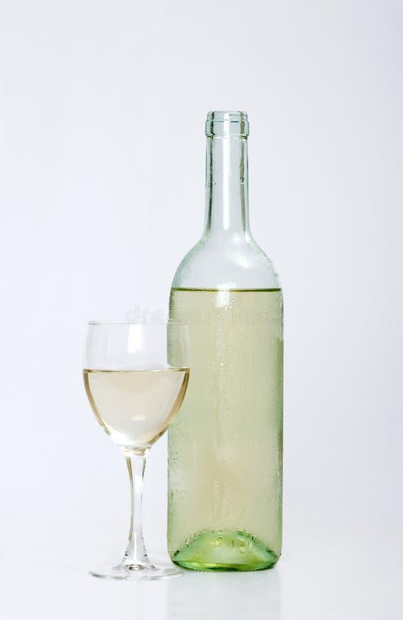 Witte wijnfles met half gevuld glas stock foto