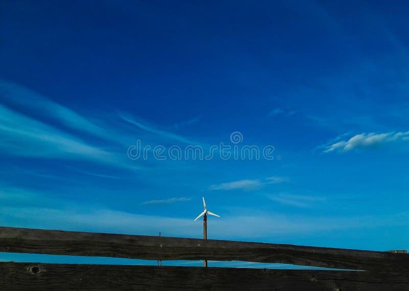 Witte windmolen tegen bewolkt-blauwe hemel stock afbeelding