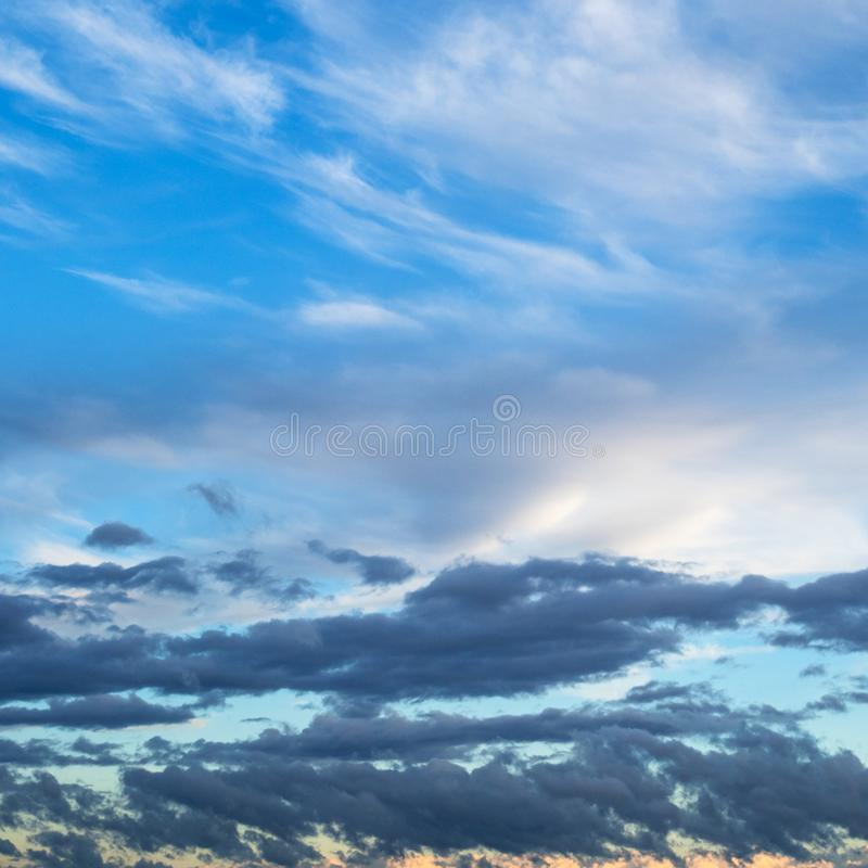 Witte wolken in blauwe hemel over donkere wolken stock afbeelding