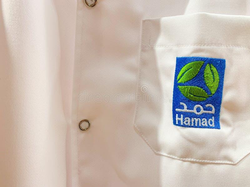 Witte workwear van een arts of een medewerker met Hamad-embleem in Arabisch en het Engels Hamad HMC is de grootste medische lever royalty-vrije stock foto