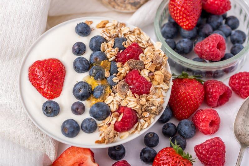 Witte yoghurt in kom met havermeel en aardbeien, bosbessen en frambozen op de bovenkant op witte achtergrond royalty-vrije stock afbeeldingen