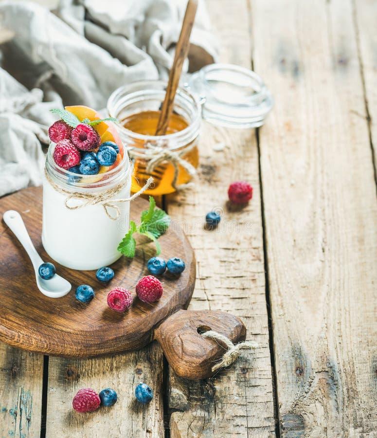 Witte yoghurt in kruik met verse bessen, munt en honing stock fotografie
