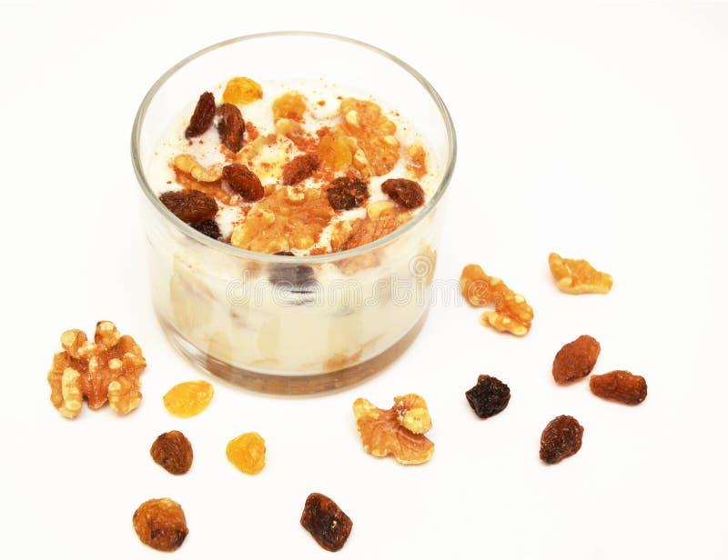 Witte yoghurt met noten en rozijn op witte achtergrond Gezond Ontbijt stock foto