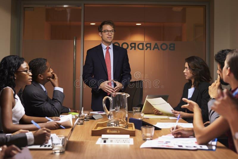 Witte zakenman die collega's op vergadering bevinden zich te richten royalty-vrije stock foto
