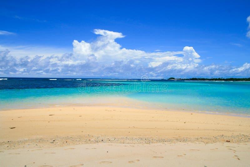 Witte zandige strandkust met de turkooise horizon van het koraalzeewater en mooie wolkenhemel bij het verwarmen van middag zonnig royalty-vrije stock foto