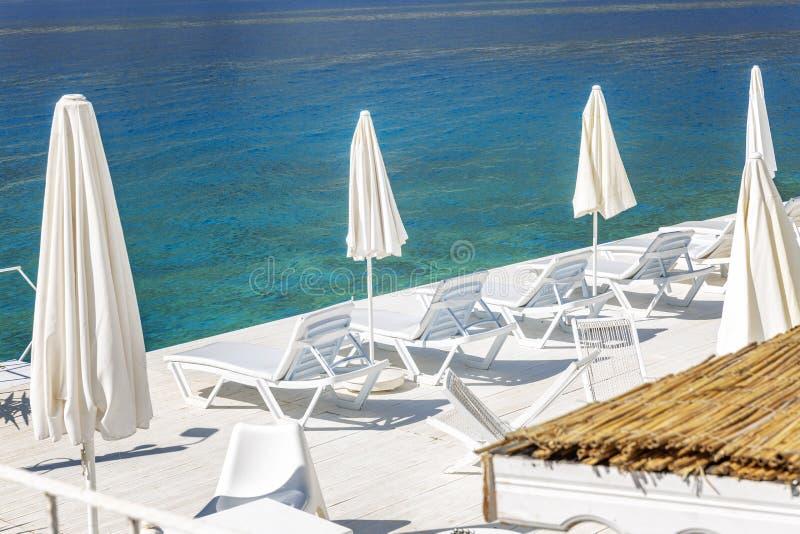 Witte zitkamerstoelen met paraplu's op de kust van het transparante overzees Luxueus logies royalty-vrije stock fotografie