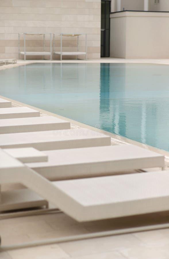 Witte zon-lanterfanters en deckchairs naast het zwembad met kristal blauw water stock fotografie