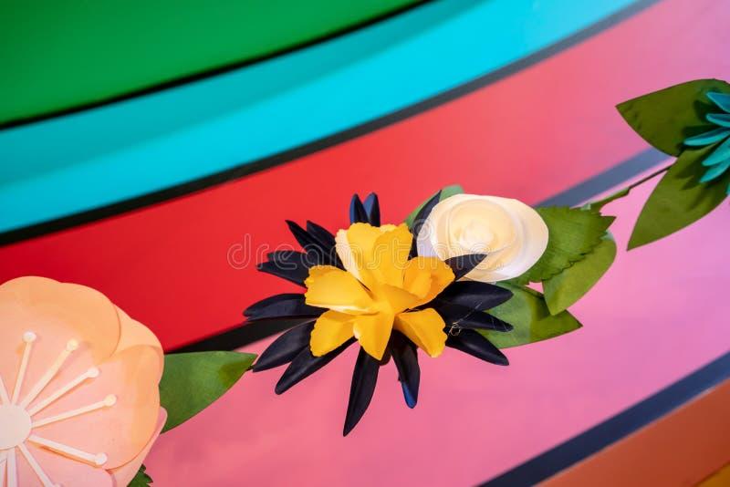 Witte, zwarte en gele document bloemen tegen regenboogachtergrond stock afbeelding