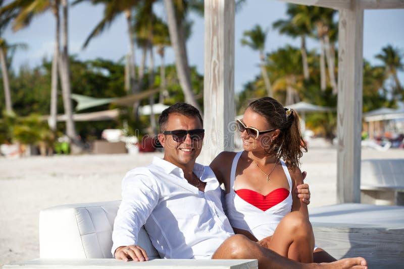 Wittebroodsweken romantisch paar in liefde het ontspannen op het luxestrand royalty-vrije stock afbeeldingen